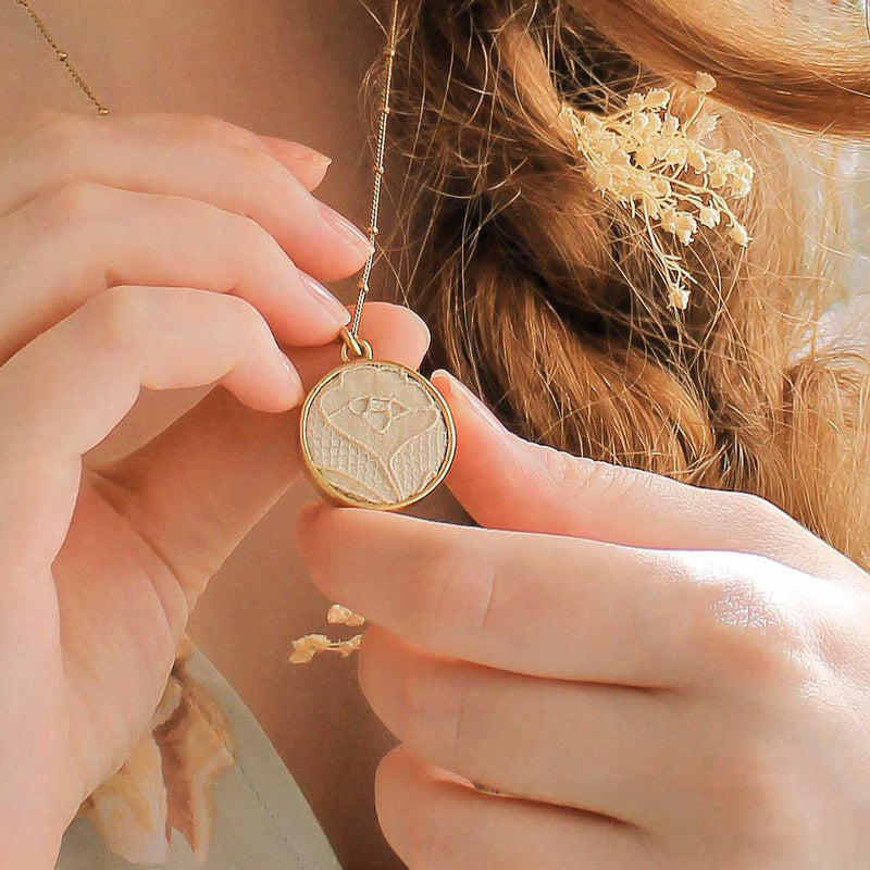 Round Gold Lace Wedding Dress Pendant Held in Hands