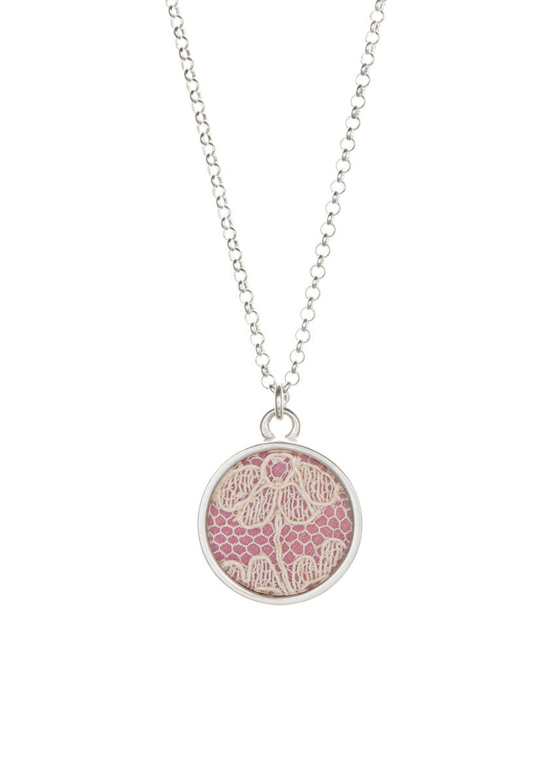 Lace keepsake necklace set in sterling silver, on pink silk.