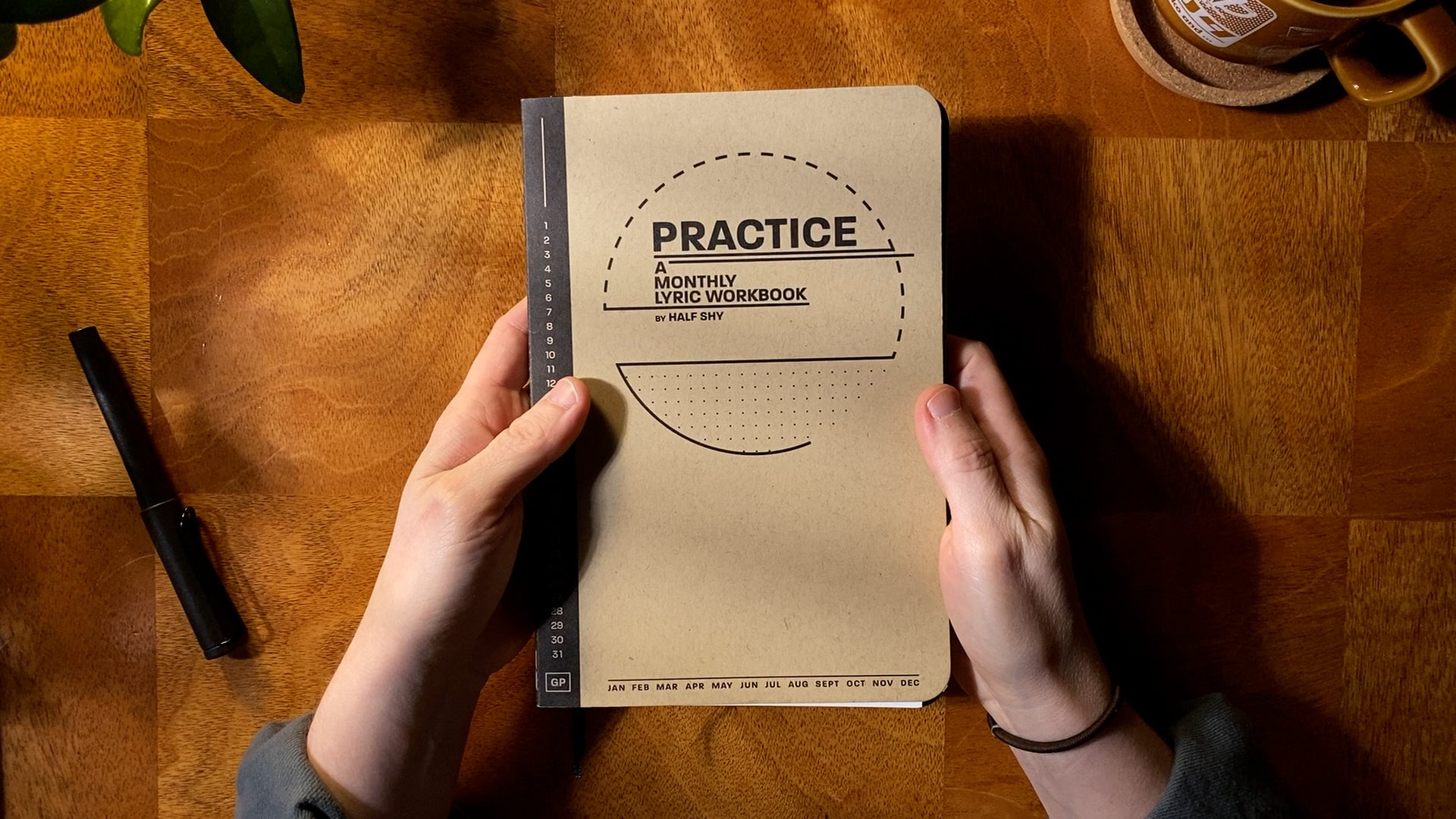 Practice Lyric Workbook cover held above a desk