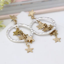 Load image into Gallery viewer, Worn gold multi star cluster and silver hoop earrings.