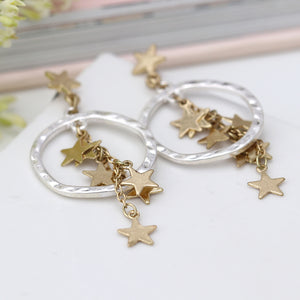 Worn gold multi star cluster and silver hoop earrings.
