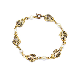 Golden bracelet with arabesques and pearls