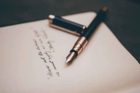 A fountain pen next to postscript in a letter.