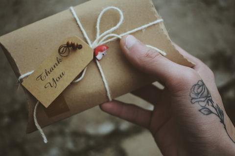ALT:person with a flower tattoo handing a thank you gift