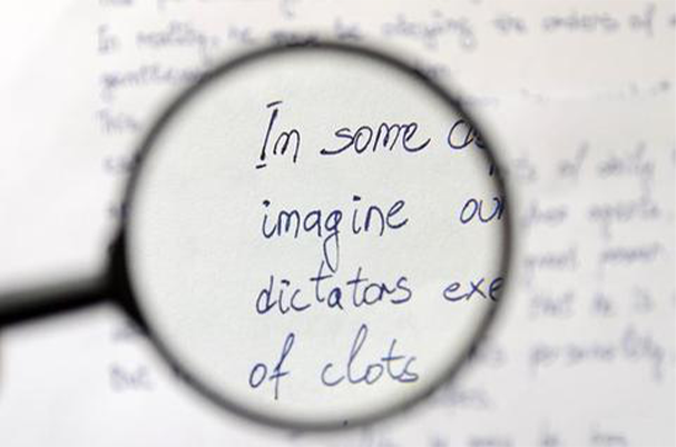 a magnifying glass looking at blue writing on a white paper