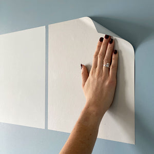 a hand placing a benjamin moore peel and stick paint sample on a bedroom wall