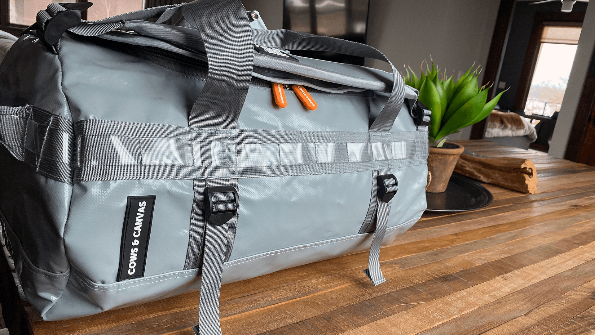 Grey Waterproof Duffle Bag With Orange Zippers Laying On Wooden Table
