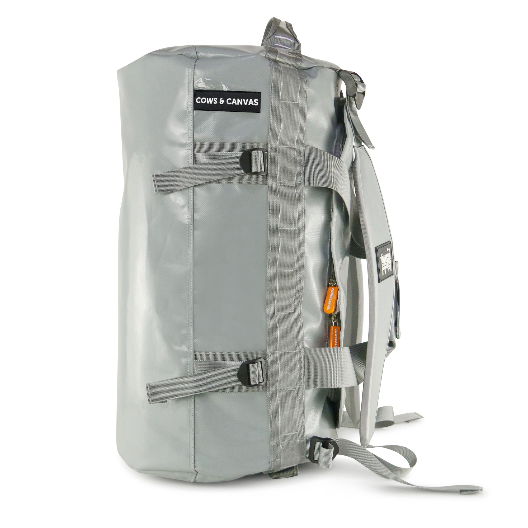 Vertical Grey duffle bag with backpack straps and orange zippers showing