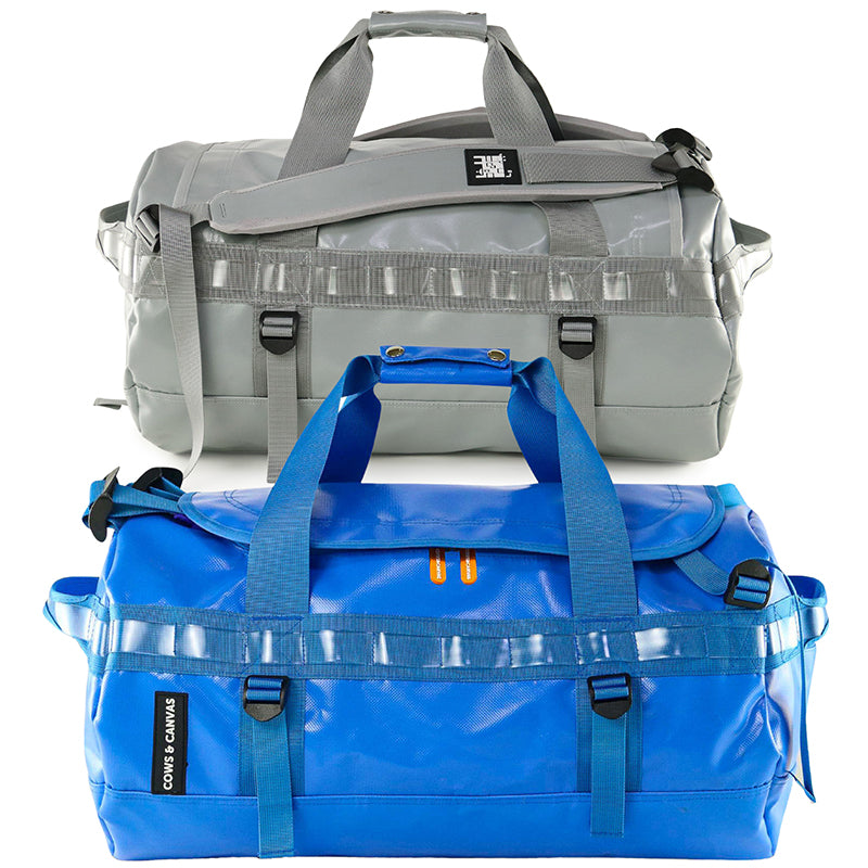 Blue and grey duffle bags showing side handles and carrying handle