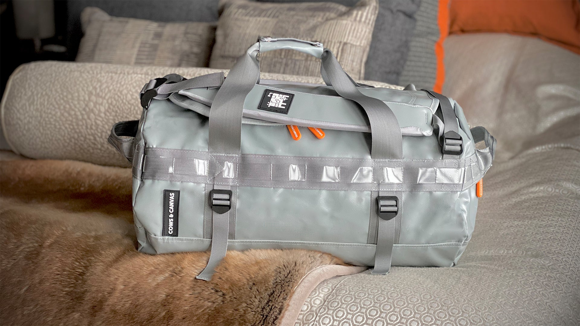 Grey Venture Bag laying on bed showing zippers and carrying straps