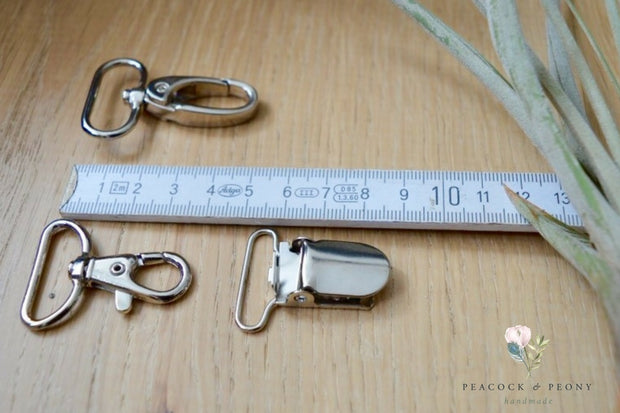 Suspender (NL: bretel) clips (35 mm) in silver and bronze