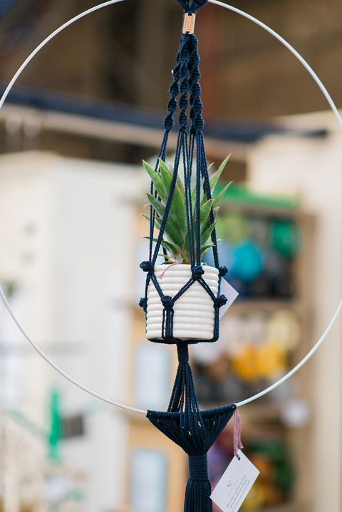 Dark blue macrame planthanger in a white Ø60cm metal circle frame