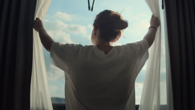 Women open and close the curtains