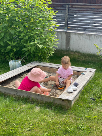 Sofie and Ella playing in sandbox in norway