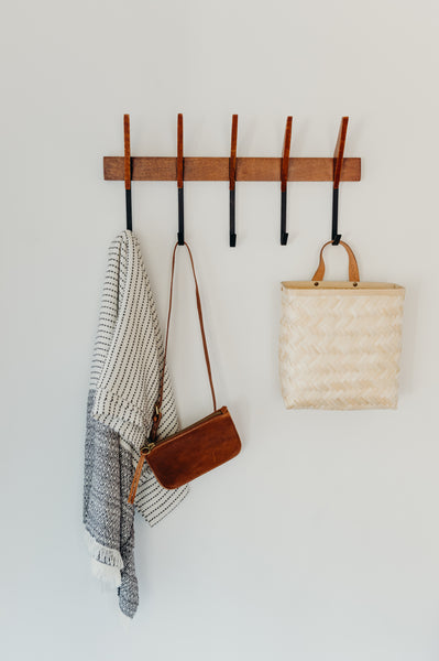 Mid-century wall rack from Urban Outfitters mounted on wall with accessories