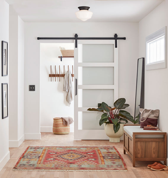Entryway decorated in scandinavian style with the 10-fin hook rack from Rejuvenation mounted in background