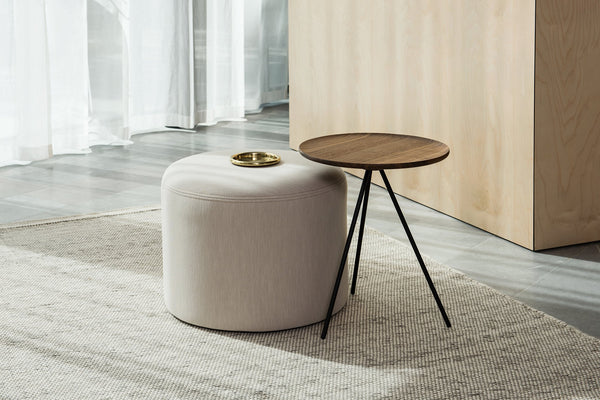 Key side table from Scandinavian design brand Hay staged with ottoman in minimalist living space