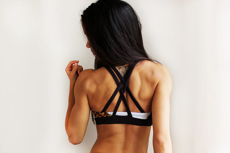 Woman with cross back black sports bra facing away from the camera
