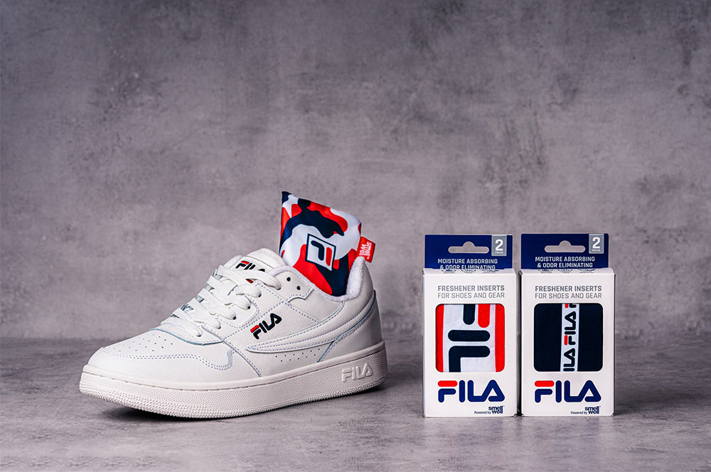 White FILA sneaker with SmellWell Active insert and two packages of SmellWell & FILA Collab Inserts