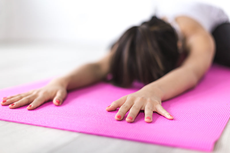 Woman in a face down yoga pose on a pink exercising mat