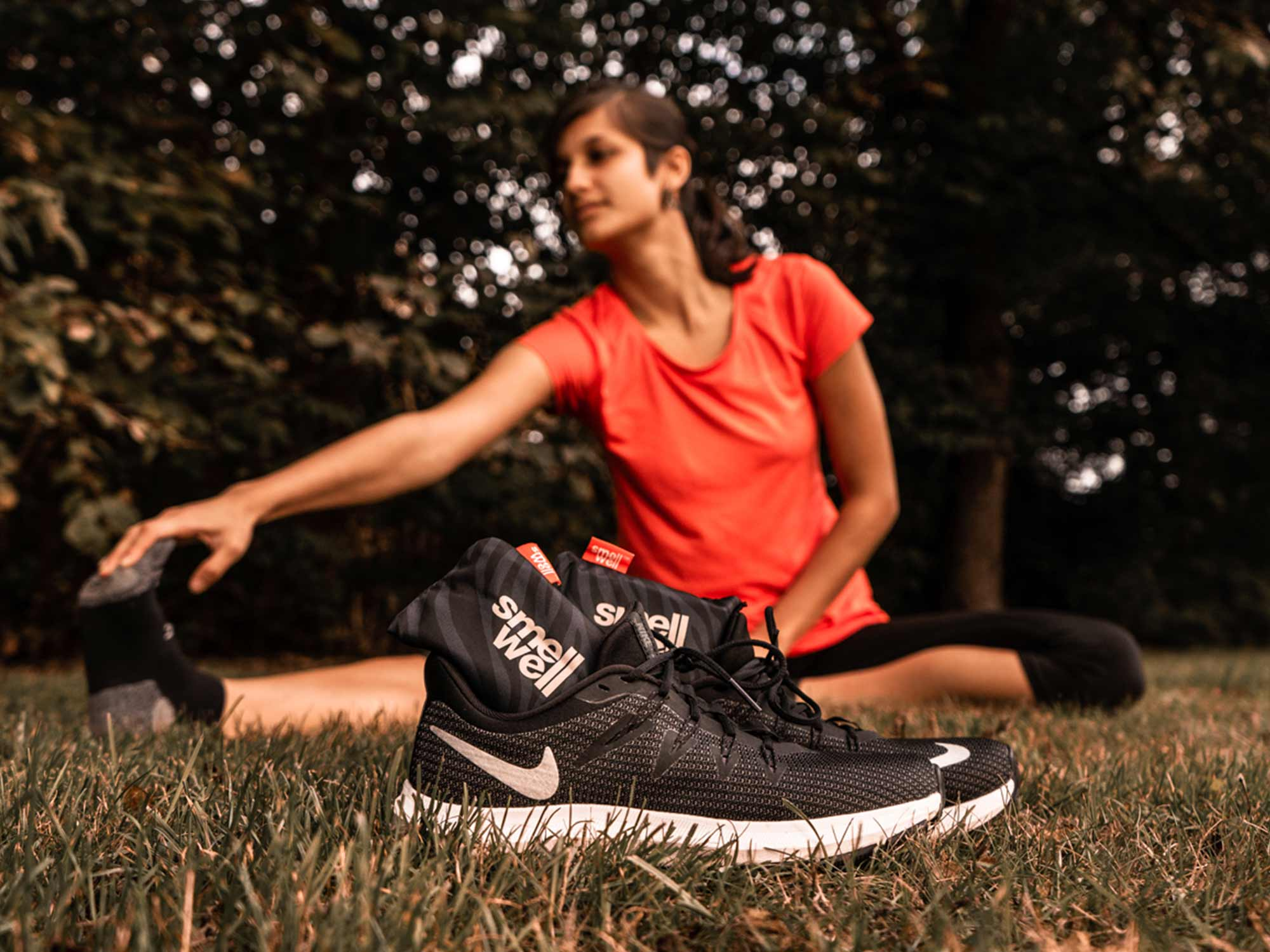 Woman stretching on a grass field behind a pair of Black Nike running shoes with black SmellWell inserts inside them.