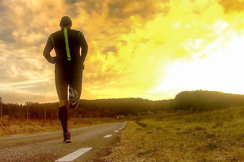 Man running on a road into the sunset