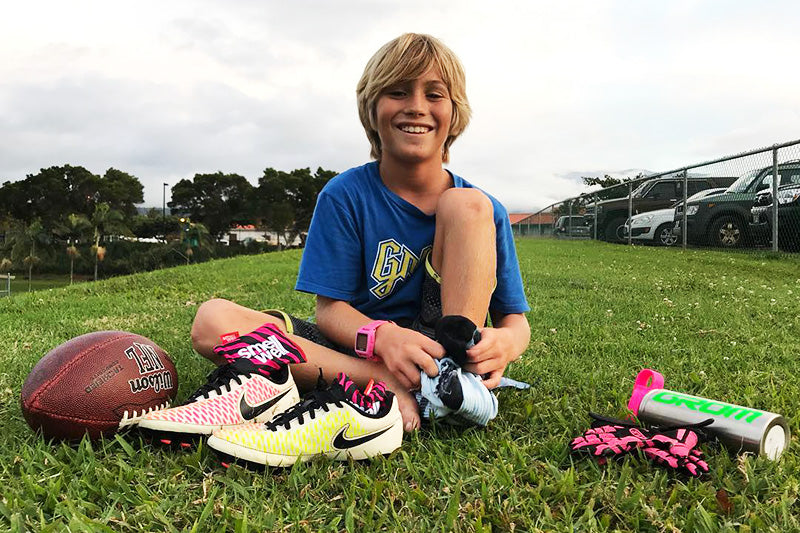 Smiling boy sitting on a grass field with a ball and a pair of Nike Football Shoes with SmellWell inserts in them.