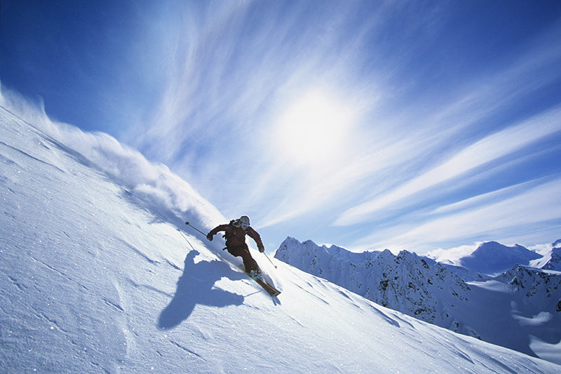 A person skiing down a hill covered with powder snow in the sun