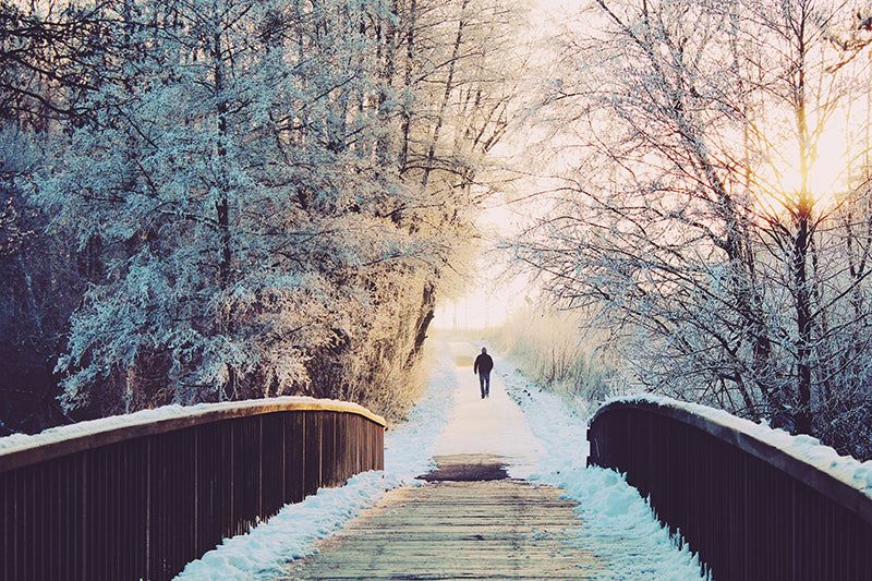 A person running or walking on the other side of a wooden bridge in a snowy landscape during sunset