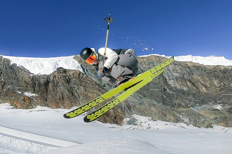 Man on skiis in the middle of a jump doing a spin