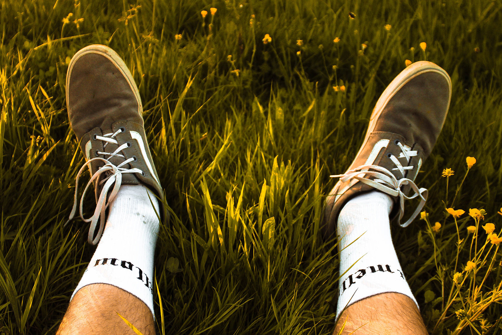 Selfshot image of a mans feet in green grass with yellow flowers