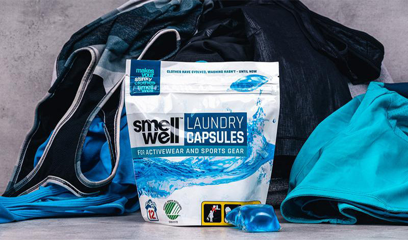 A bag of SmellWell Laundry Capsules in front of a pile of dirty workout clothes.