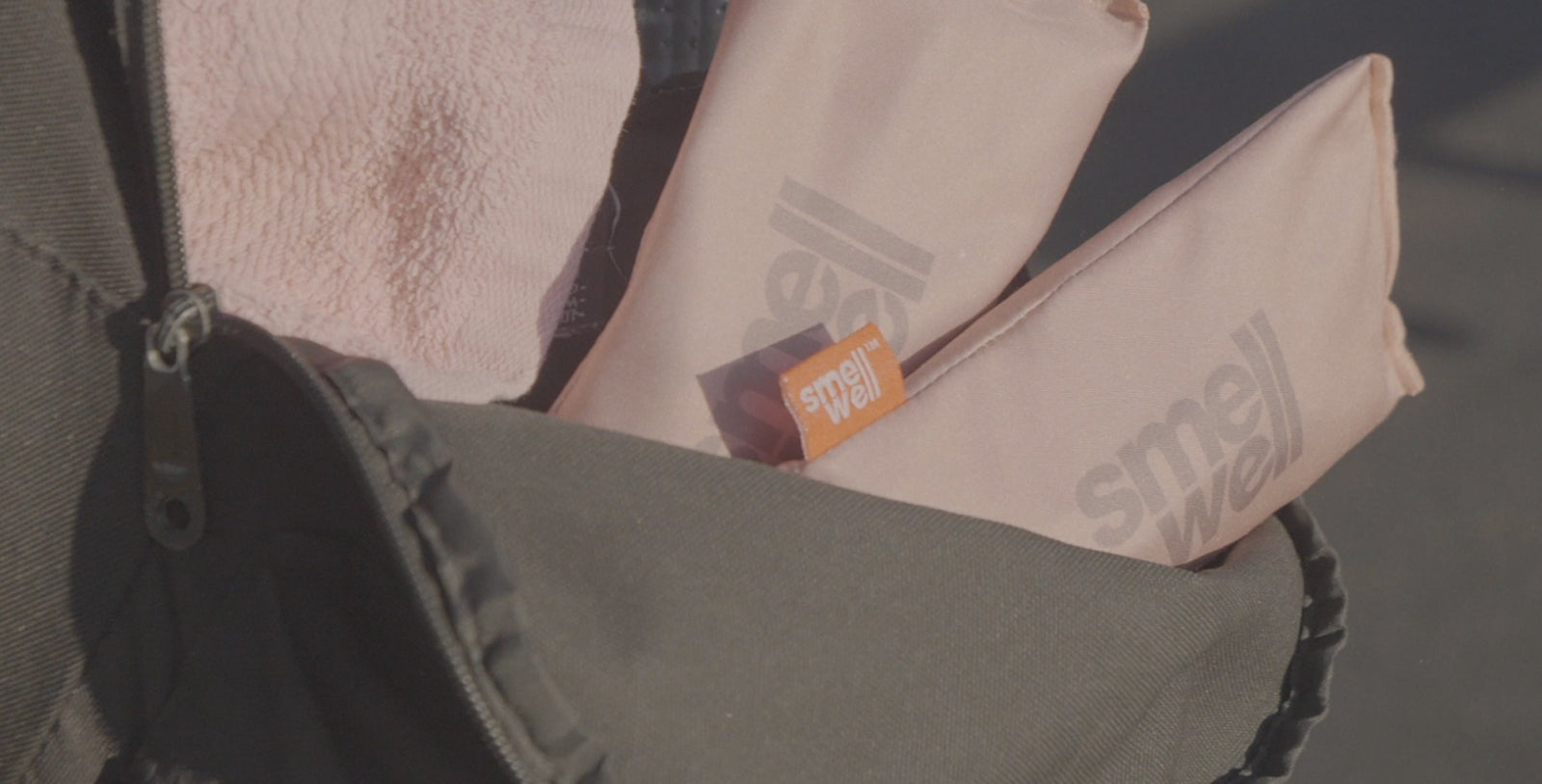 A pair of SmellWell Freshener Inserts sticking out of a bag of training clothes.