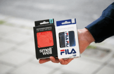 A hand holding a package of SmellWell Active - Geometric Orange and a package of SmellWell Active - FILA