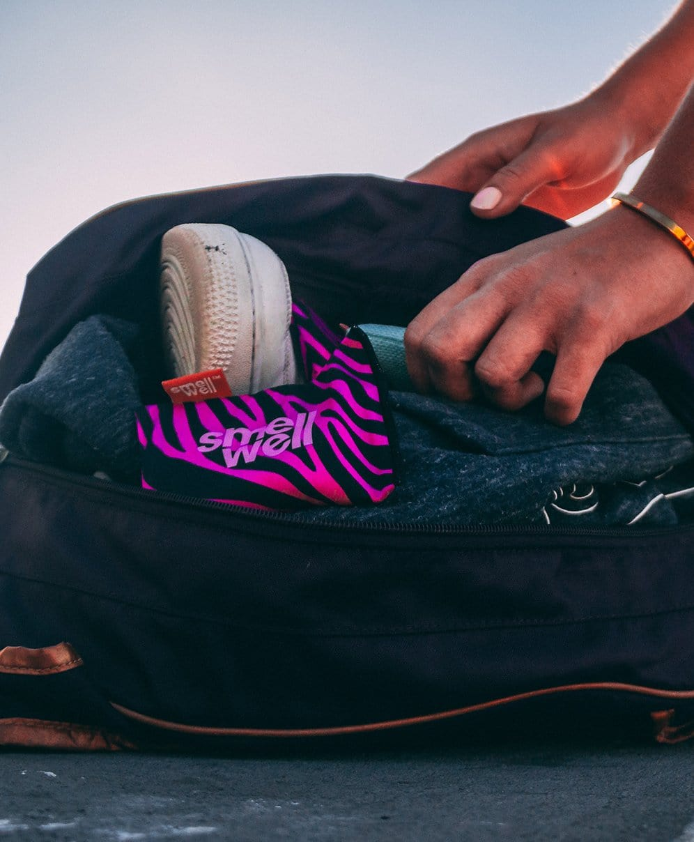 SmellWell Active - Pink Zebra freshener inserts lying in a bag with dirty gym clothes
