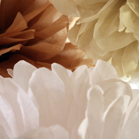 Tissue paper poms by PomAdore in Seaside Cottage colors of white and beige.