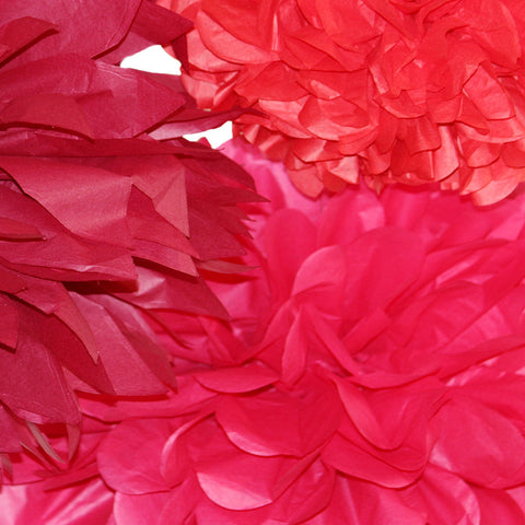 A gorgeous color combination of red tissue paper poms by PomAdore.