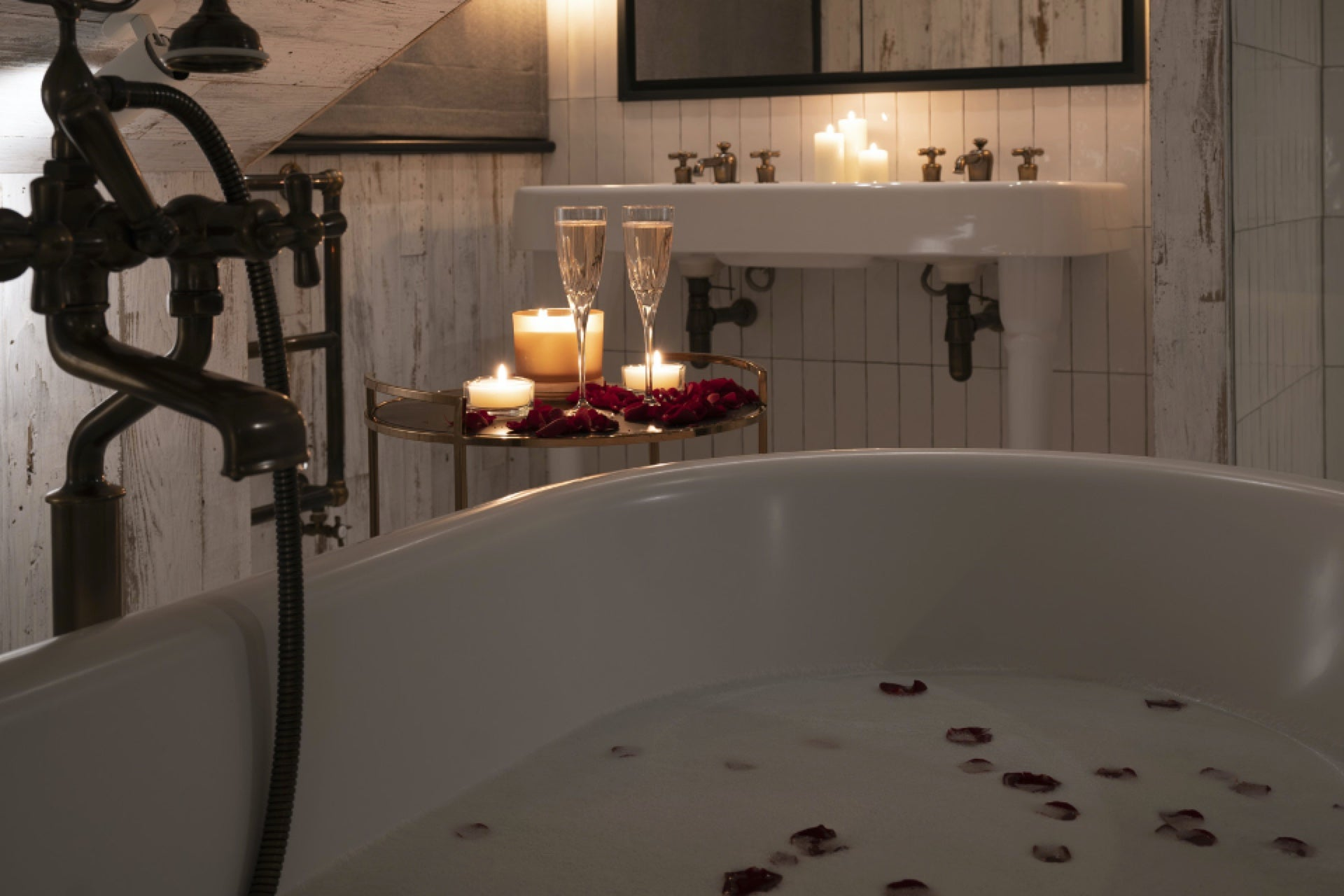 Candle lit bathroom with rose petal bubble bath and champagne