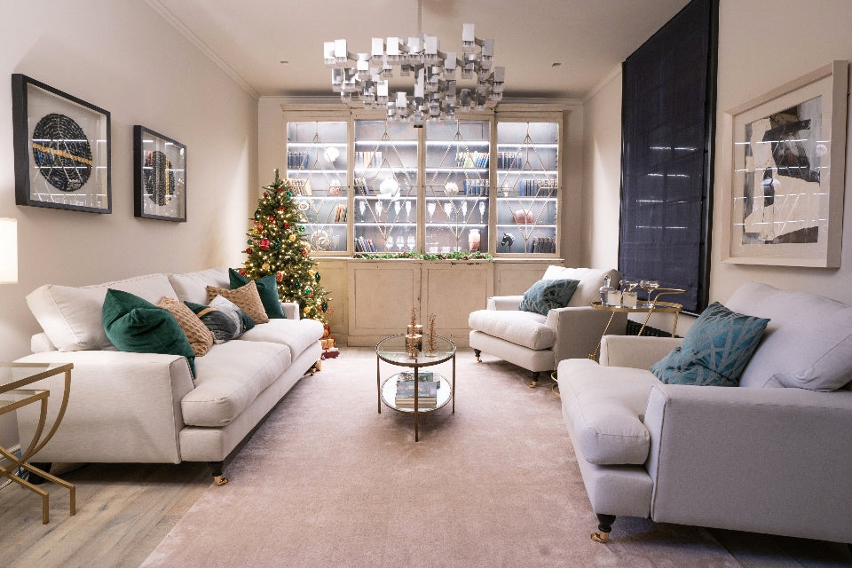 London townhouse reception room with art deco dresser, white sofas and a christmas tree