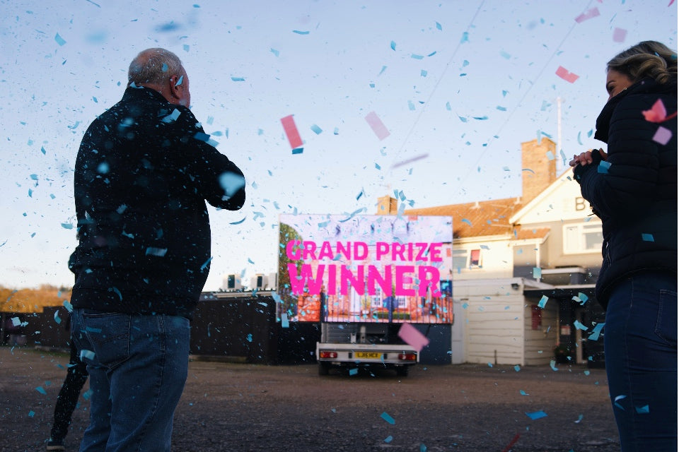 Confetti surrounding large TV screen reading 'Grand Prize Winner' with the winner and presenter of the Omaze Million Pound House Draw