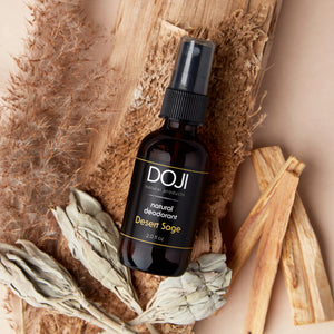 Doji natural deodorant, desert sage scent, overhead shot with sage smudge, palo santo wood pieces, and vetiver.