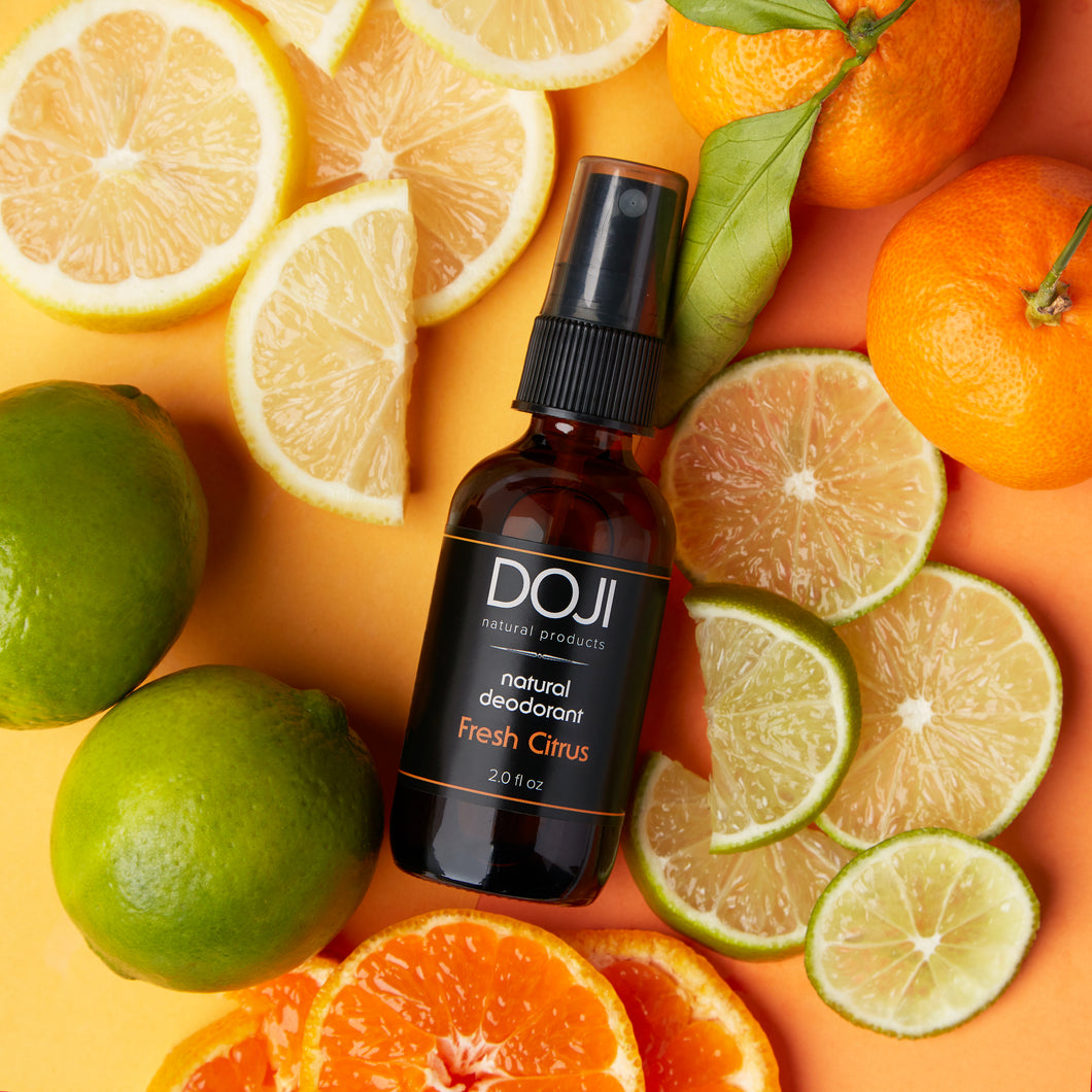 Doji natural deodorant, fresh citrus scent, overhead shot with cut limes, lemons, oranges, tangerines, mandarins.