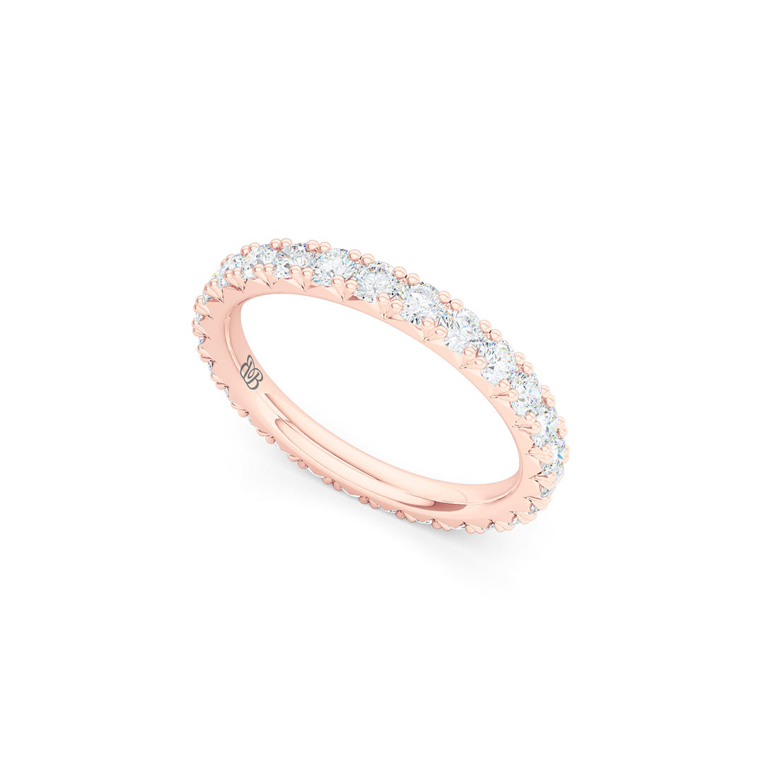 Classic French fishtail-set Diamond Eternity Wedding Ring. Hand-fabricated in Romantic Rose Gold and round brilliant diamonds. Free Shipping for All USA Orders.  BASHERT JEWELRY | Boca Raton, Florida