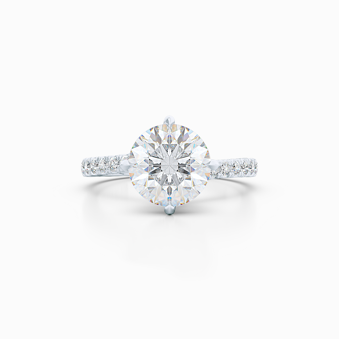 East-West, four prong, Round Solitaire. Recessed diamond halo. Diamond adorned shoulders. Hand-fabricated in Sustainable Solid White Gold. Available in Moissanite by Charles & Colvard or Lab-Grown Diamond by Diamond Foundry. | Made in Boca Raton, Florida. 15 Day Returns. Free Shipping USA. | Bashert Jewelry