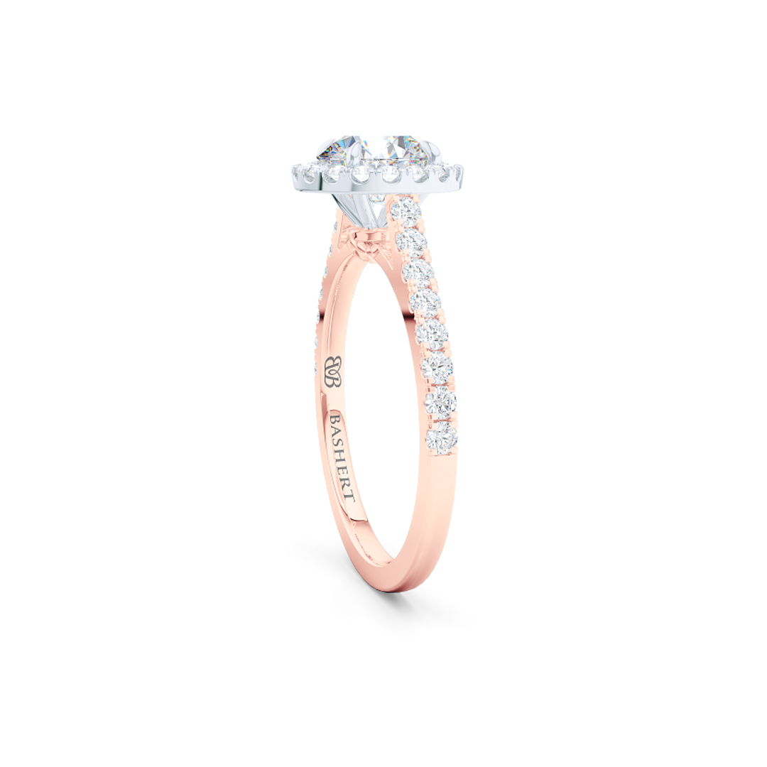 Classic Round Halo Engagement Ring, hand-fabricated in two-tone metal - Romantic Rose Gold and Precious Platinum. The center stone is a Round Brilliant, Forever-One Moissanite by Charles and Colvard. Dazzling diamond micro pavè set shoulders and crown. Free Shipping USA. 15 Day Returns | BASHERT JEWELRY | Boca Raton, Florida.