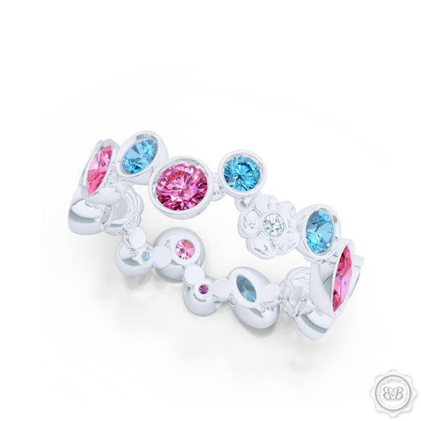 Unique Floral Motif Eternity Ring, Handcrafted in White Gold, Sky Blue Topaz, and Pink Tourmalines. Customize it with Birthstones or Anniversary gems of Your Choice. Free Shipping USA. 30Day Returns. BASHERT JEWELRY | Boca Raton, Florida