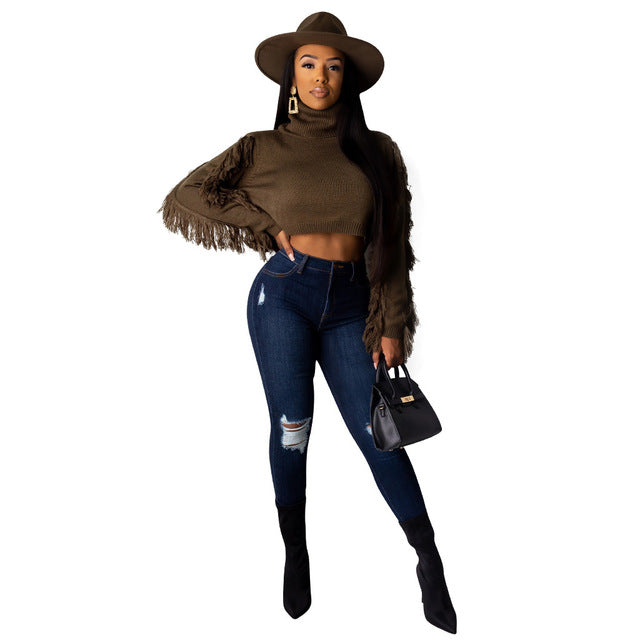 Channel your inner girl power with our Urban Rider Knitted Pullover. This remarkable look features a high neckline and tasseled long sleeves with a crop top cut. Achieve effortless style by simply pairing the pullover with dark denim and over the knee boots.