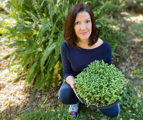 Louise in garden with sunflower sprouts
