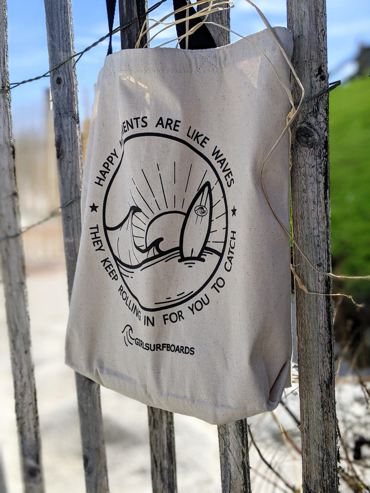 happy moments tote bag hanging on fence