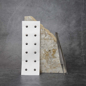 A sheet of body magnets and a pair of tweezers propped up against a slab of marble. The body magnets are a sheet of 12 small round magnets that are placed on the body using the tweezers. The tweezers have a ridged grip and blunt, flat tips.